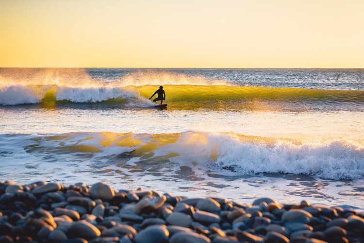 Surfer on the ocean wave at sunset or sunrise. Winter surfing in wetsuit