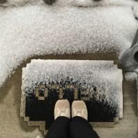 """Pieds sur mon tapis d'entrée noir avec l'inscription """"Hello"""" parsemé de neige"""