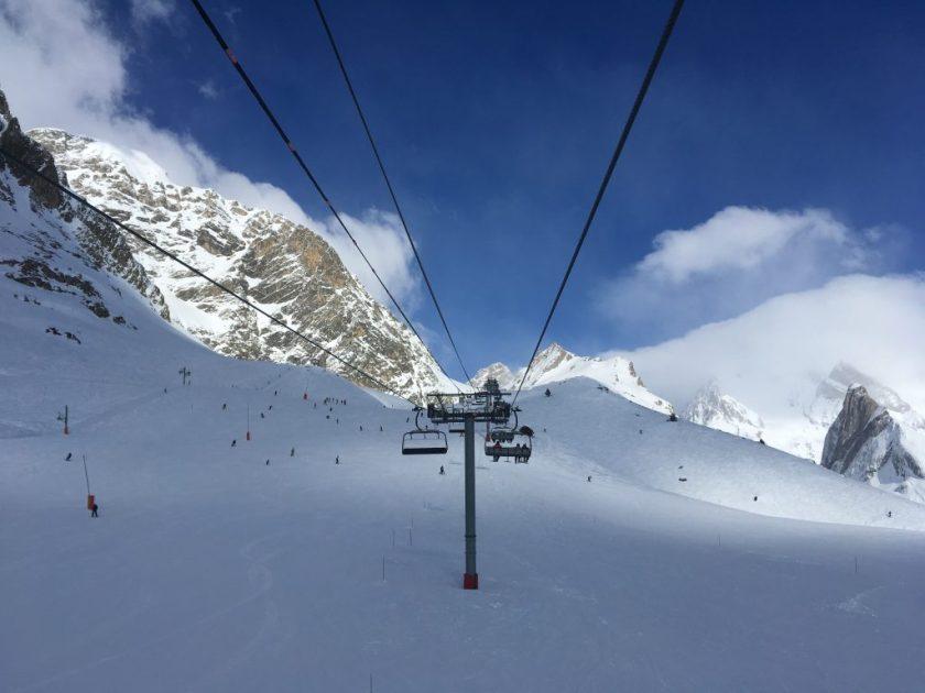 Assise dans une remontée mécanique, on apercoit au loin l'horizon et le ciel bleu avec la neige en dessous nos pieds.