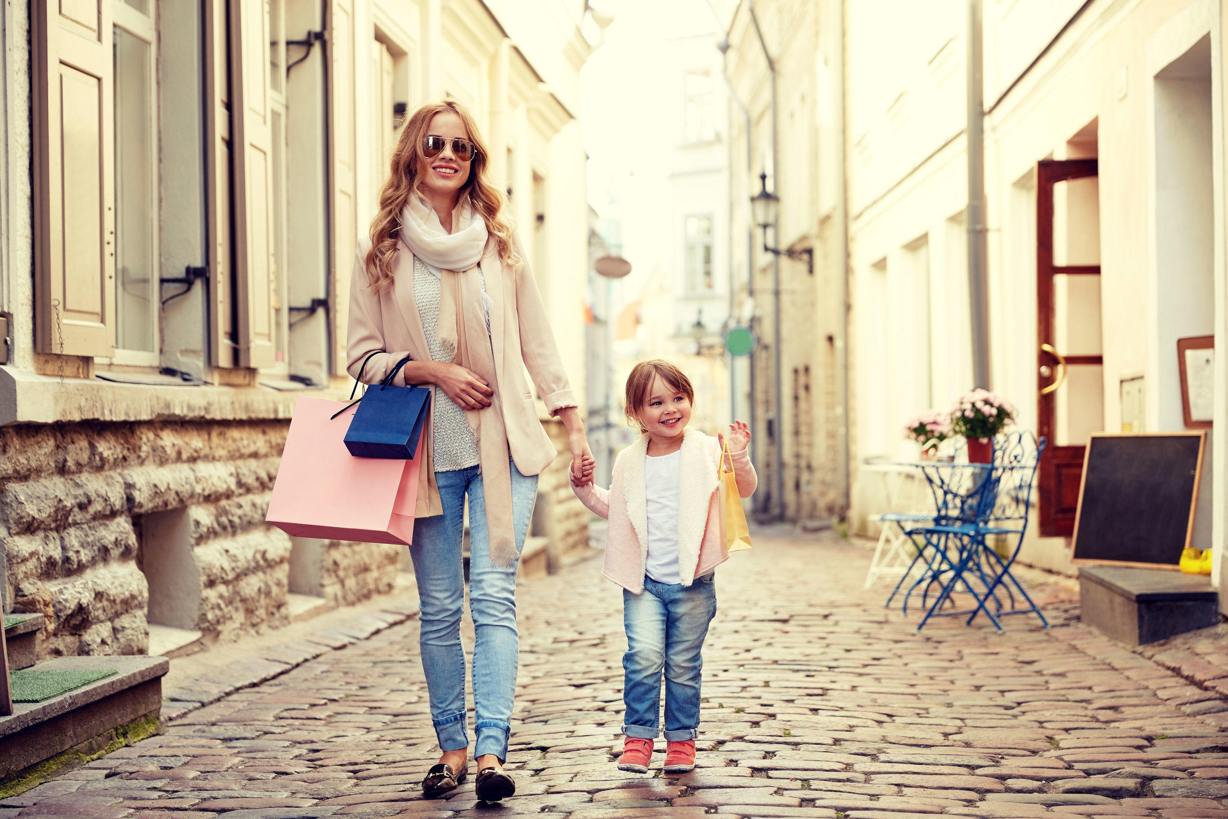 70767464 – happy mother and child with shopping bags in city