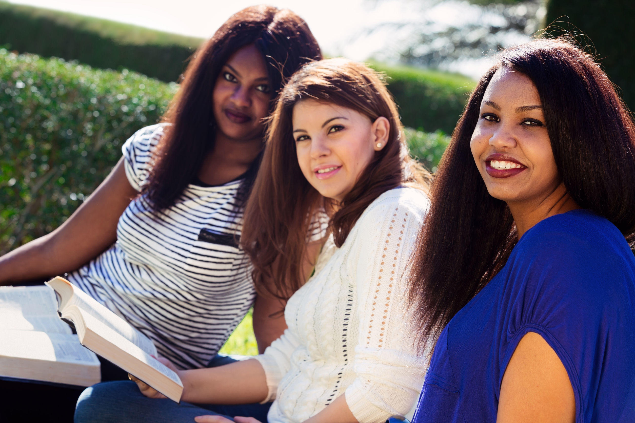 30851213 – three christian girls studying the bible and looking at the camera