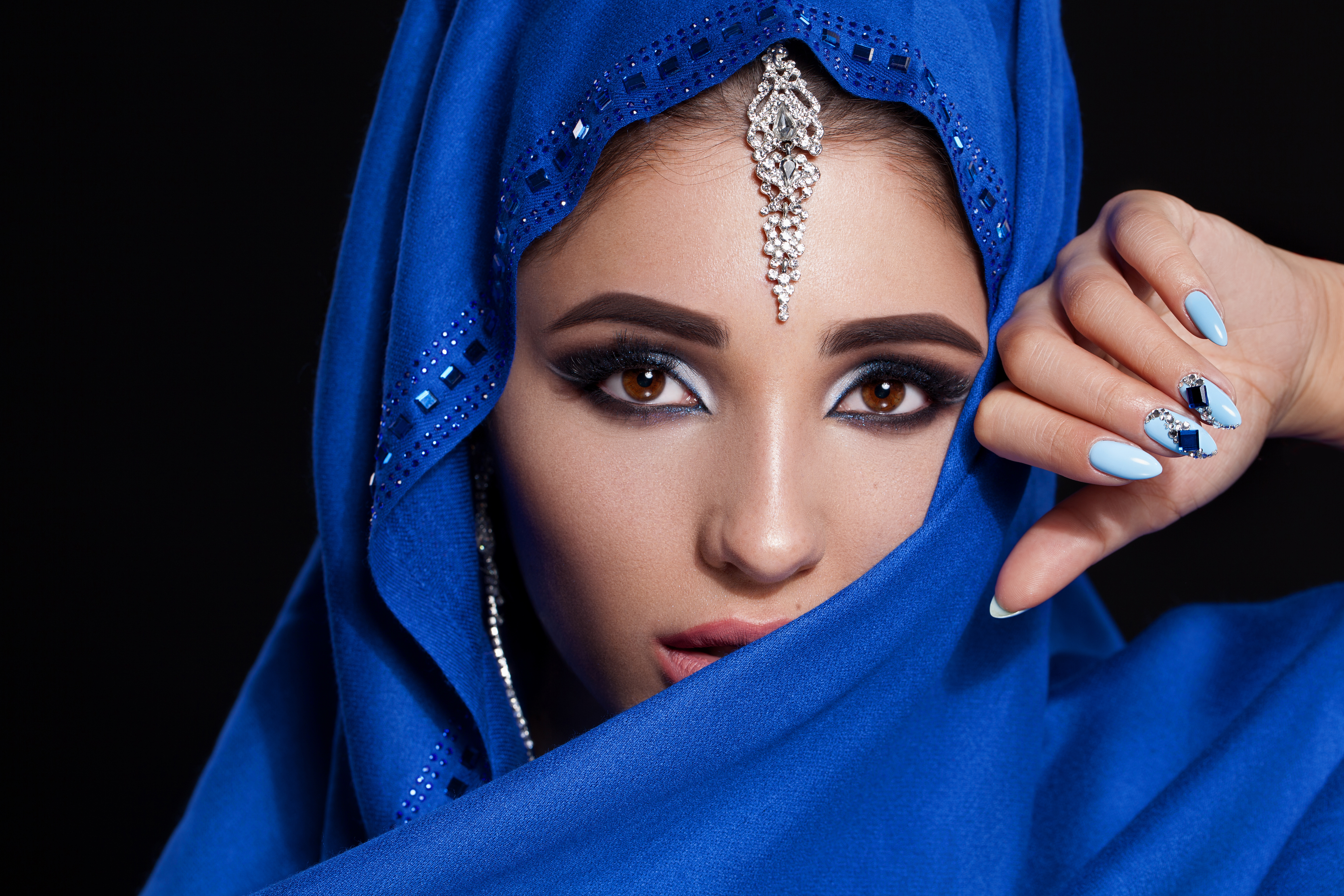 Gorgeous Young East Woman face portrait in hijab. Beauty Model Girl with bright eyebrows, perfect make-up, touching her face. Traditional. Isolated on black background. Smokey eyes. Jewelry on her face