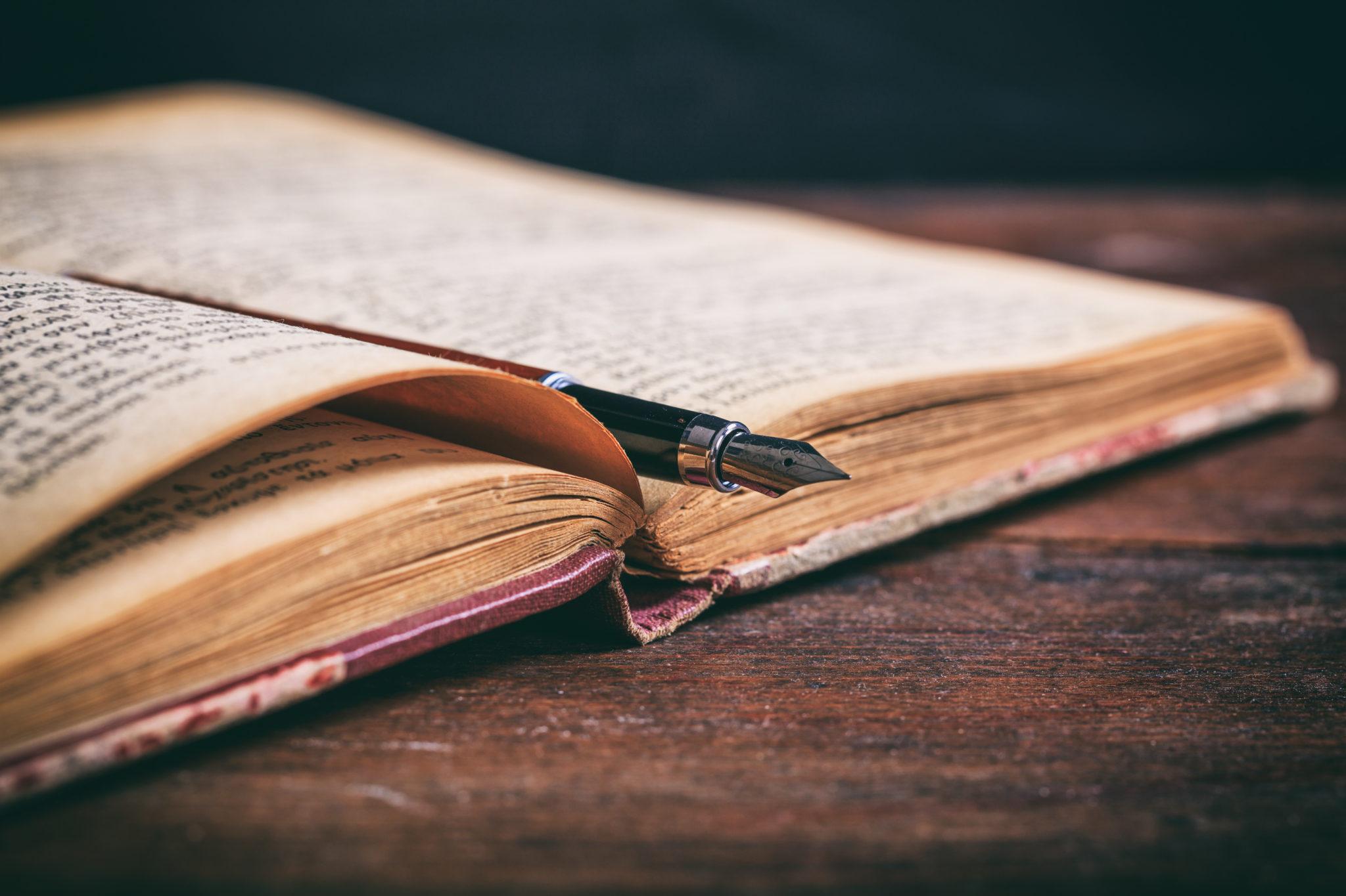Vintage book and ink pen on a wooden desk