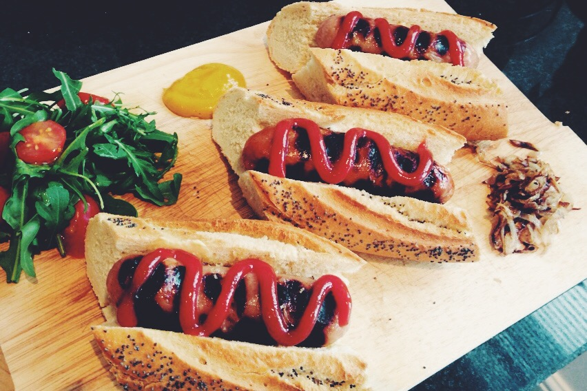 Grandads Sausages Posh Dogs served with poppy seed baguettes, rocket salad and fried shallots