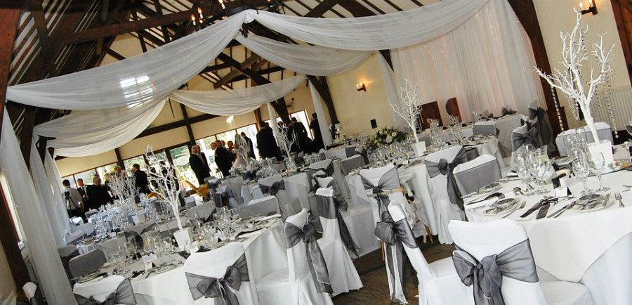 gold chair covers with black sash patio furniture cushions cover hire bows wedding table swagging venue striking and white organza double over cotton