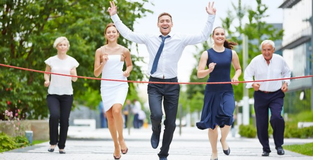 Business man is the winner while running with a business team to the finish line