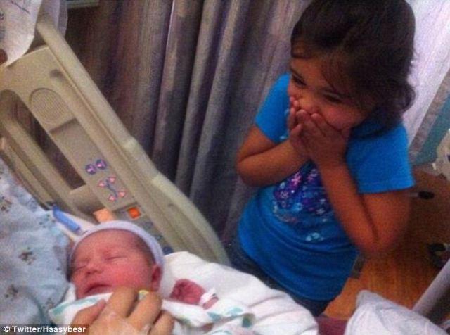 Una pequeña niña que conoce por primera vez a un recién nacido