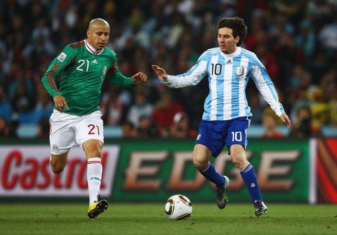 JOHANNESBURG, SOUTH AFRICA - JUNE 27: Lionel Messi of Argentina is challenged by Adolfo Bautista of Mexico during the 2010 FIFA World Cup South Africa Round of Sixteen match between Argentina and Mexico at Soccer City Stadium on June 27, 2010 in Johannesburg, South Africa. (Photo by Quinn Rooney - FIFA/FIFA via Getty Images)