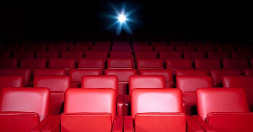 Sala de cine vacía con asientos rojos.
