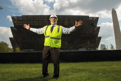 Lonnie Bunch, founding director of the Smithsonian's National Museum of African American History and Culture, stands in front of the museum on the National Mall in Washington, D.C., July 26, 2016. The institution is due to open in September. The outer shell, or corona, was designed to match the 17-degree angle of the capstone of the Washington Monument, behind. (photo by Allison Shelley for Smithsonian magazine)