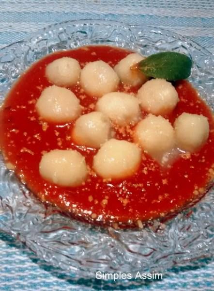 Esse nhoque é conhecido como gnudi e é feito com semolina e ricota e servido com molho de tomate.