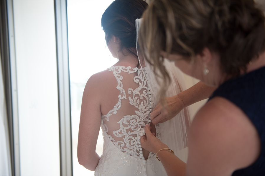 Mother of bride buttoning wedding dress