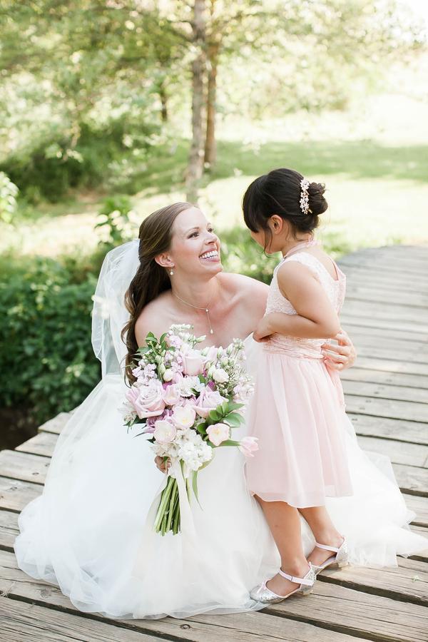 bride posing flower girl