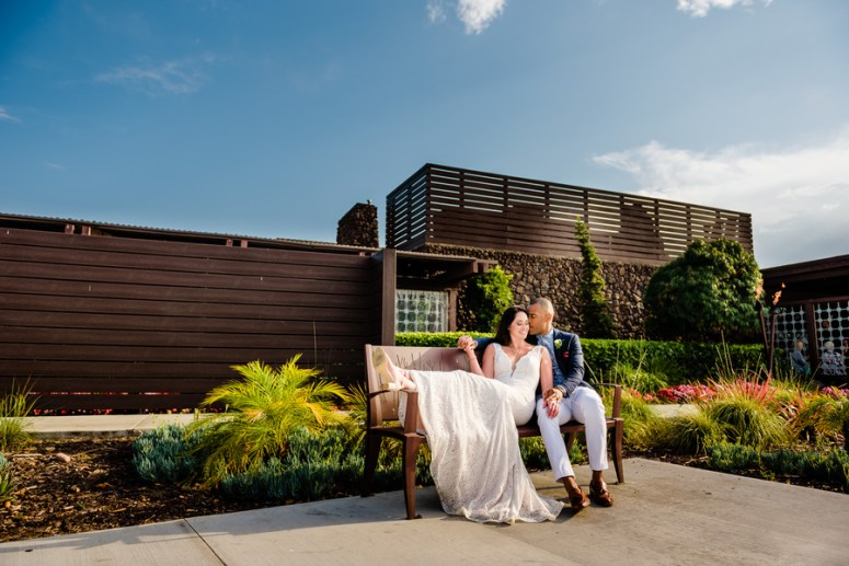 Bride and Groom pose on Bench