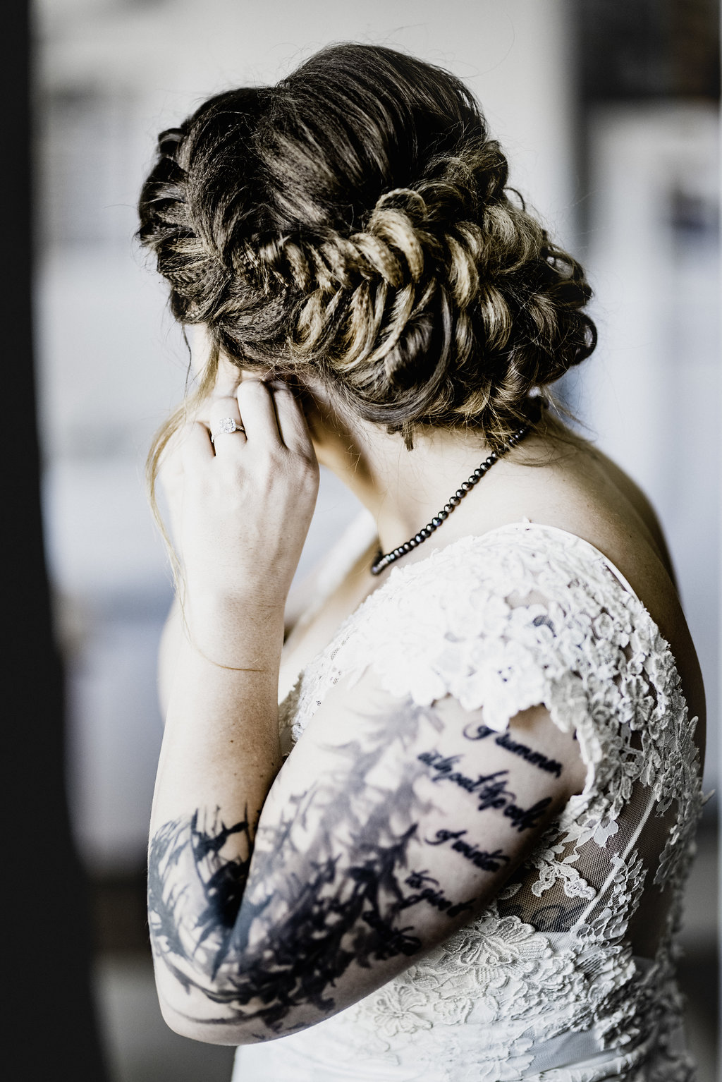 bride putting on earrings, bride with tattoos