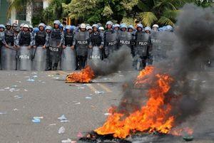 © Agence France-Presse - - Hondurascy policjańci formują kordon, żeby zablokować zwolenników wygnanego prezydenta Hondurasu, Manuela Zelayę