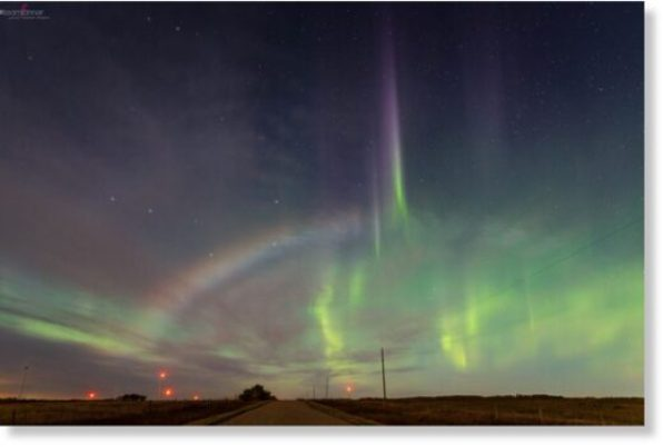 A moonbow appears against a backdrop of emerald-green northern lights over Castor, Alberta, on Sunday night