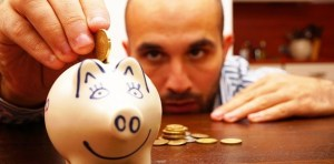 A man is saving money by putting coins in a piggy bank
