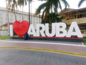 amc sitting in front of the I love Aruba sign