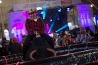 A RedBlacks fan rides the mechanical bull at the Grey Cup tailgate party photo Renee Doiron