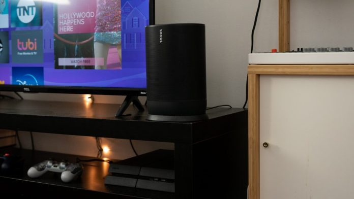 The Sonos Move speaker on a TV stand next to a Roku TV and a Playstation controller