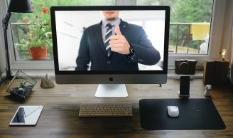 Office with a computer monitor and thumbs up on the screen from a man in a suit.