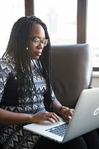 photo of a woman in professional attire using a laptop