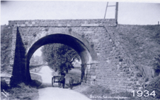 Postcard image of railway bridge near station with horse and cart