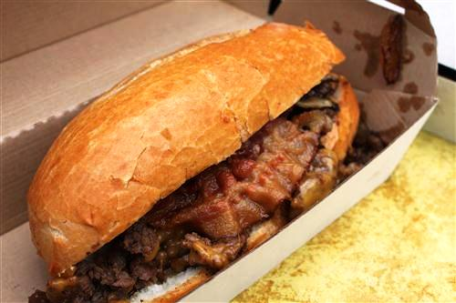 Bacon Cheese Steak Sandwich: Angus rib-eye topped with carmelized onions, bacon, and cheddar cheese.
