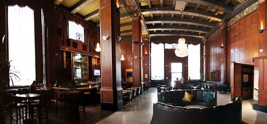 The cavernous interioir of The Federal Bar, Long Beach.  Towering columns, wood paneling, and chandeliers add to the ambience.