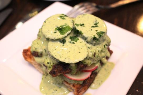 The open faced lamb burger smothered kale tahini sauce.