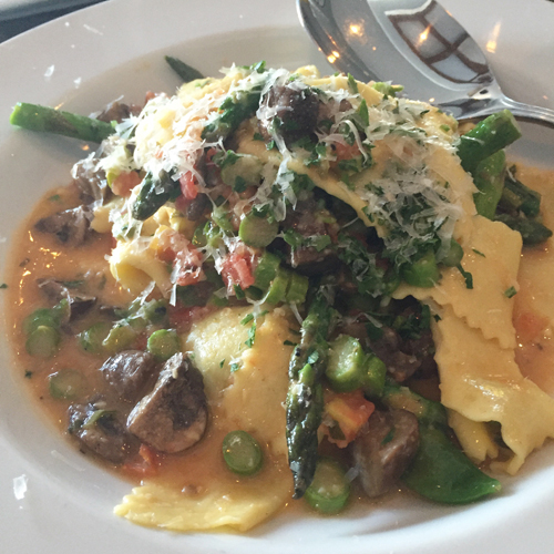 Hand cut pasta squares with fresh tomatoes, asparagus and mushrooms in a white wine sauce