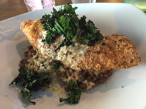 Southern fried catfish draped over gold rice and red peas and topped with charred greens