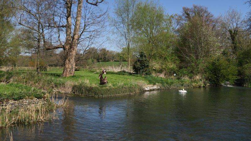 A mill pond with an interesting sculpture - could it be one of the  Cirencester Hares escaped?