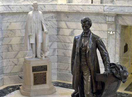 """In this Wednesday, Aug. 5, 2015 file photo, a statue of Jefferson Davis, left, looks towards a statue of Abraham Lincoln in the Rotunda of the Kentucky State Capitol in Frankfort, Ky. Did 620,000 die, as Northerners would have it, in a noble quest to save the union and end slavery _ the nation's horrific original sin? Or was the """"War Between the States"""" a gallant crusade to limit federal power, with slavery playing a lesser part, as Southerners insisted? (AP Photo/Timothy D. Easley)"""