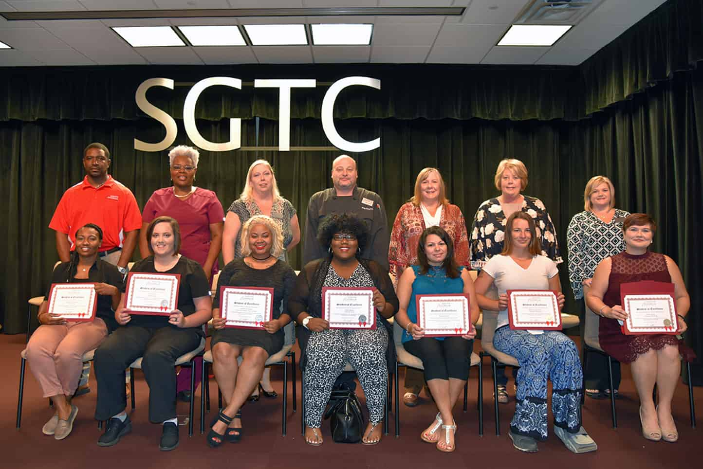 Student of Excellence nominees sit in chairs holding certificates in front of their nominating instructors. Seated left to right: : SGTC Student of Excellence nominees Lashanda Bobbs, Francis Gill, Anaiah Kirkland, Tiara Reese, Melisa Flakes, Shannon Cranford and Sheri Ariail. Standing left to right: Nominating Instructors Xavier Jackson, Dorothea Lusane-Mckenzie, Teresa McCook, Ricky Watzlowick, Jaye Cripe, Lynn Lightner and Christine Rundle.