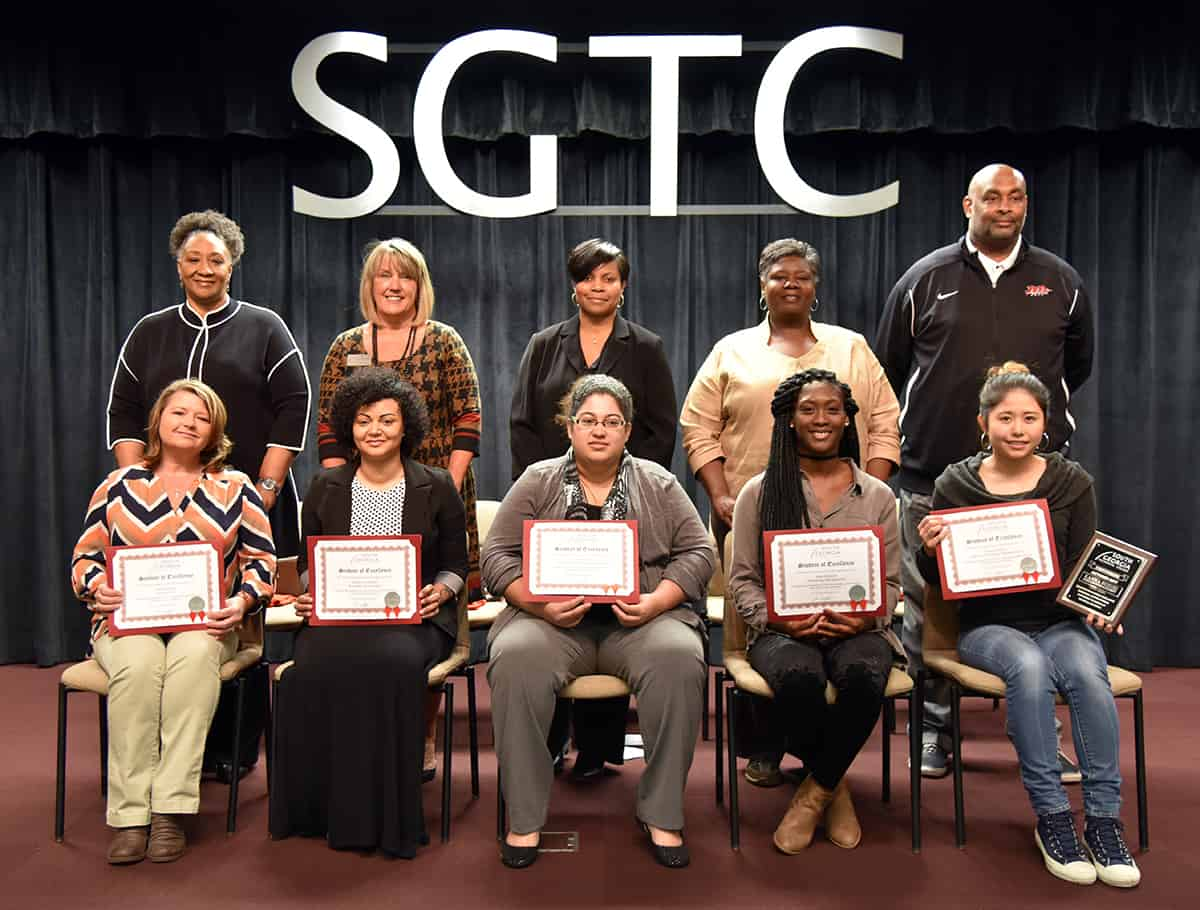 Sitting from left to right are Student of Excellence nominees Hope Griggs, Adrienne Clayton, Angelica Sims, Kayla Bowens, and winner Kanna Suzuki. Standing from left to right are nominating instructors: Brenda Hudson Boone, Donna Lawrence, Andrea Ingram, Mary Cross and Travis Garrett.