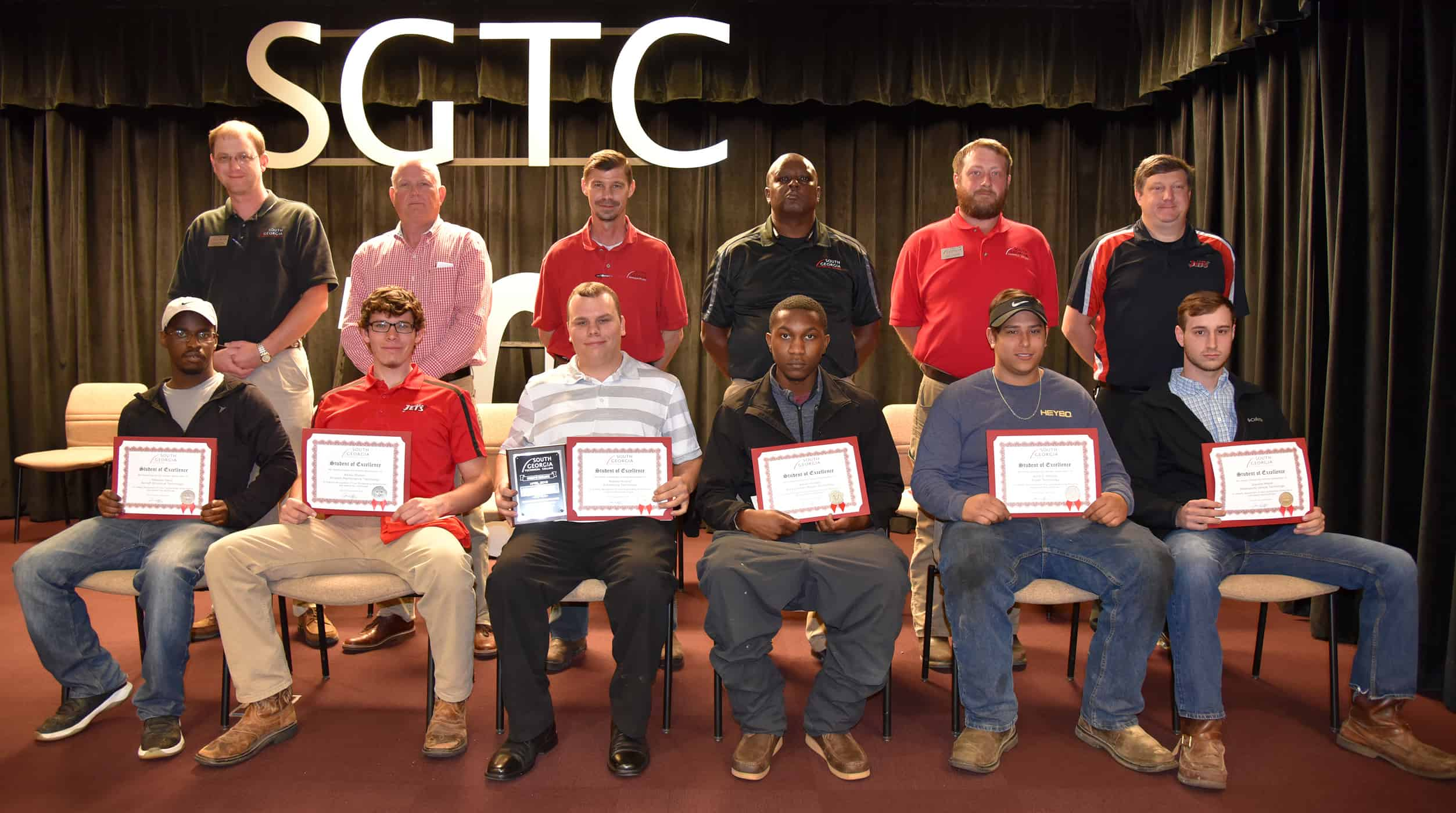 Six males sit in a row of chairs holding certificates. Behind them stand six males.