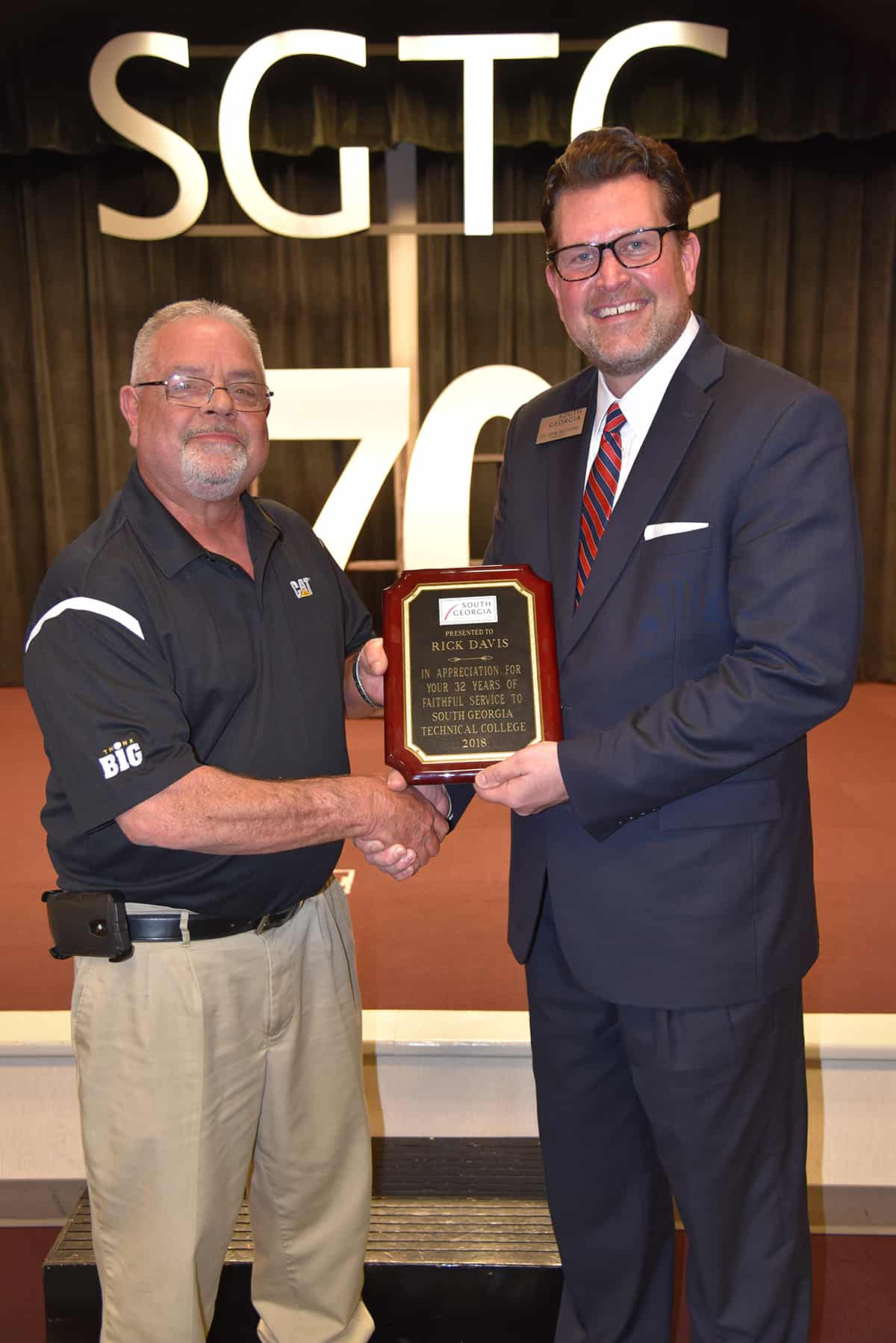 Dr. John Watford (r) is shown above presenting Rick Davis with a plaque in honor of his more than 30 years of service with South Georgia Technical College.