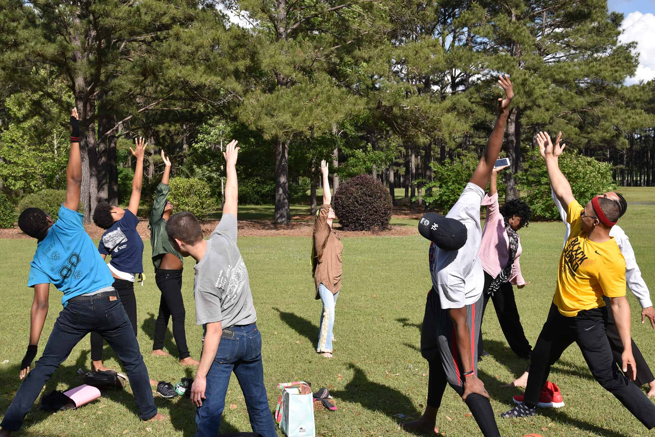 Students stand in a circle doing a yoga pose.