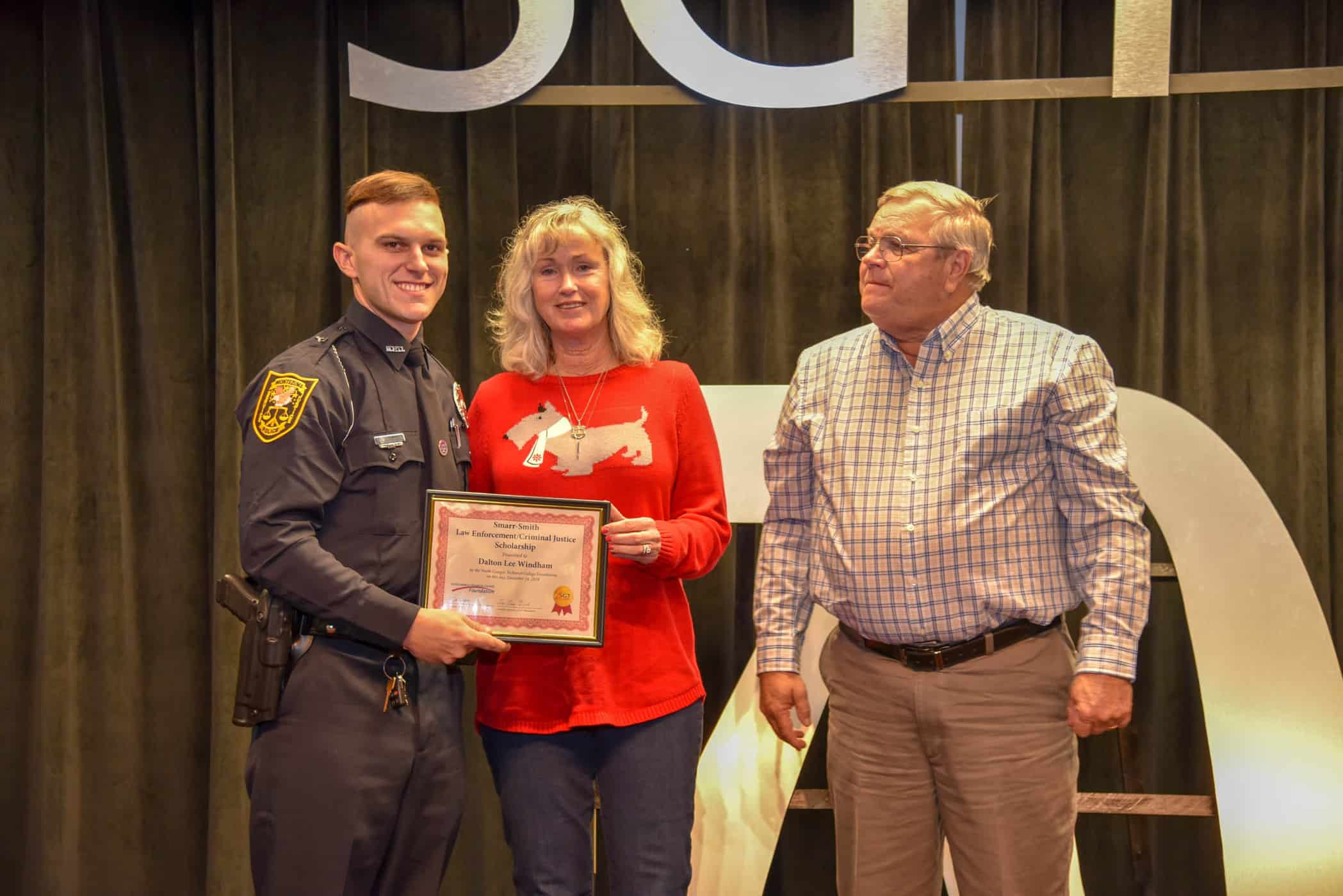 Paul and Sharon Smith Johnson are shown above (right to left) presenting Dalton Windham of the Montezuma Police Department with a Smarr-Smith Criminal Justice Scholarship.