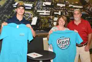 """A potential CAT student and his family are showing off the FREE """"Changing Lives"""" t-shirts presented during the Orientation/Registration Day."""