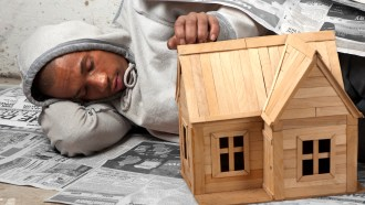 A homeless street kid rest on the pavement next to a toy house he built to remind him of his dream.