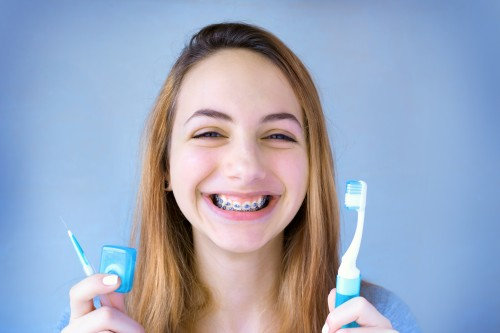 Girl Smiling with Toothbrush and Floss