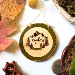 Explore wood slice ornament with with tree and mountain design