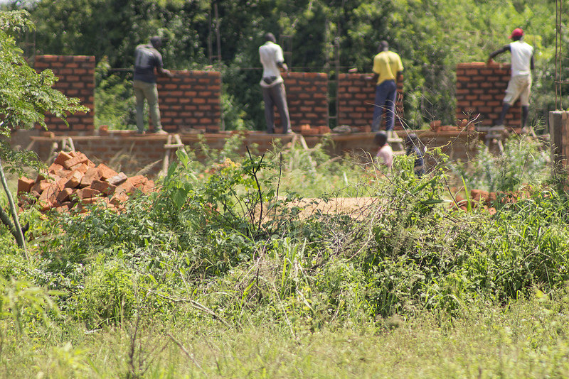Four Ugandan men lay bricks that will be the future dormitories for Global Leaders' boarding students.