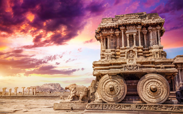 Ancient Hampi Monument Stone Chariot in the the Vittala Temple Complex with dramatic skies during sunset in Unesco Heritage Hampi town, Karnataka.