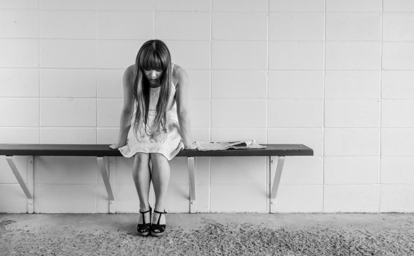 distressed girl on bench in empty room