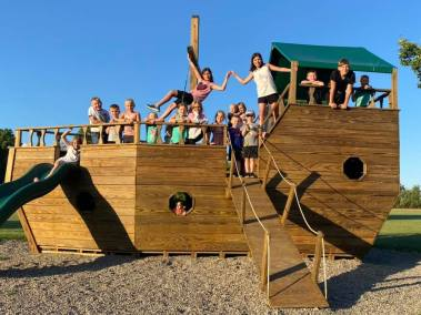 Kids on a Wooden Pirate Ship in Playground