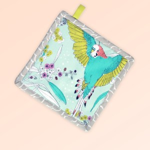 Square insulated pot holder. The fabric is Australian organic cotton with an aqua background and budgerigars and small native flowers in pastel colours. The trim around it is soft grey with a tab for hanging.